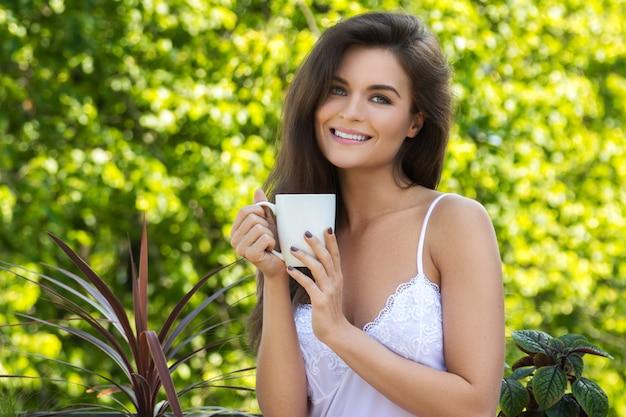 Mulher feliz tomando café na varanda ou no jardim Foto Premium