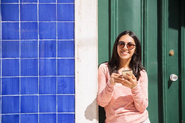 Mulher feliz, usando, smartphone, ao ar livre Foto gratuita