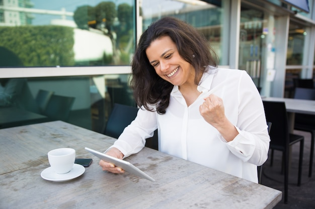 Mulher feliz usando tablet e comemorando sucesso no café ao ar livre Foto gratuita