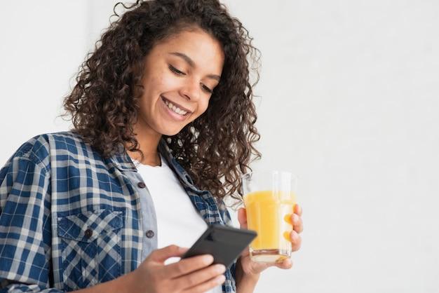 Mulher feliz usando telefone e segurando o suco de laranja Foto gratuita