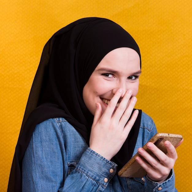 Mulher feliz vestindo camisa jeans usando smartphone no fundo brilhante Foto gratuita