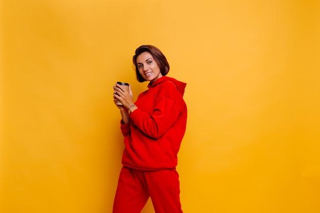 Mulher feliz vestindo roupas quentes de inverno, moletom com capuz e calças, se aquecendo com uma xícara de café quente Foto gratuita