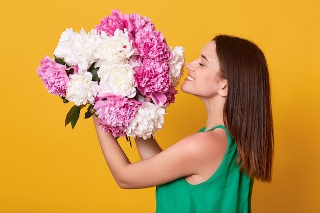 Mulher feliz vestindo traje verde segurando e cheirando flores peônias brancas e rosa Foto gratuita