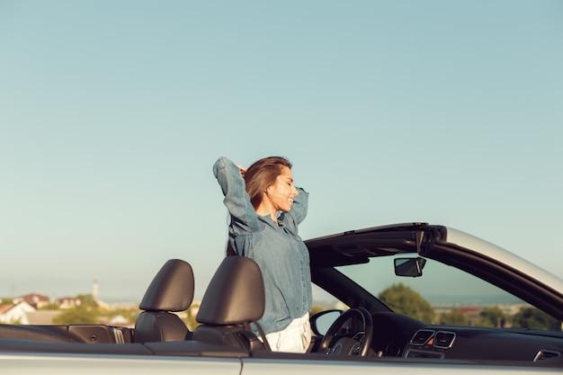 Mulher feliz viajante no carro cabrio Foto Premium