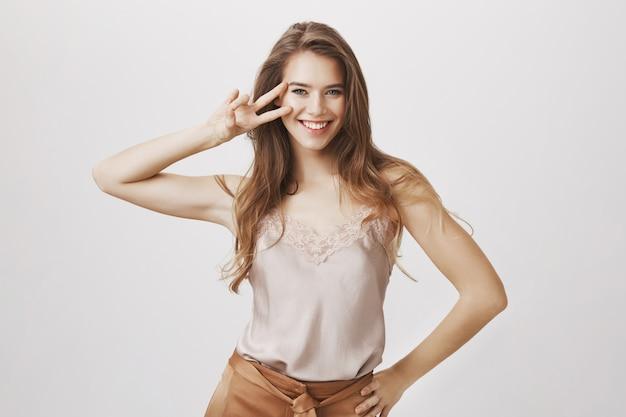 Mulher feminina sensual mostra sinal de paz e sorrindo Foto gratuita