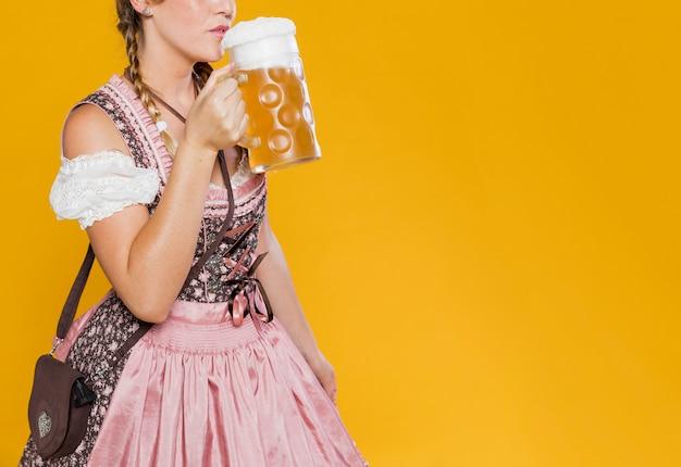 Mulher festiva em traje pronto para beber cerveja Foto gratuita
