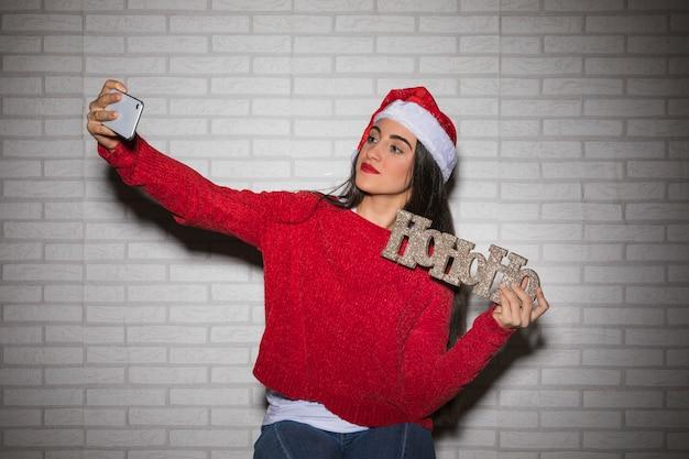 Mulher festiva tomando selfie Foto gratuita