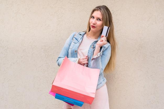 Mulher, ficar, com, bolsas para compras, e, cartão crédito, em, parede Foto gratuita
