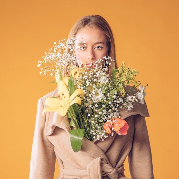 Mulher, ficar, com, buquê flores, em, agasalho Foto gratuita