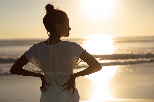 Mulher, ficar, com, mãos quadrils, praia Foto gratuita