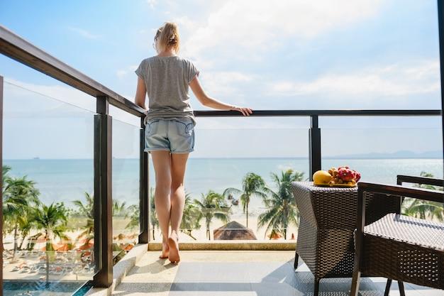Mulher ficar na varanda do resort de hotel Foto Premium