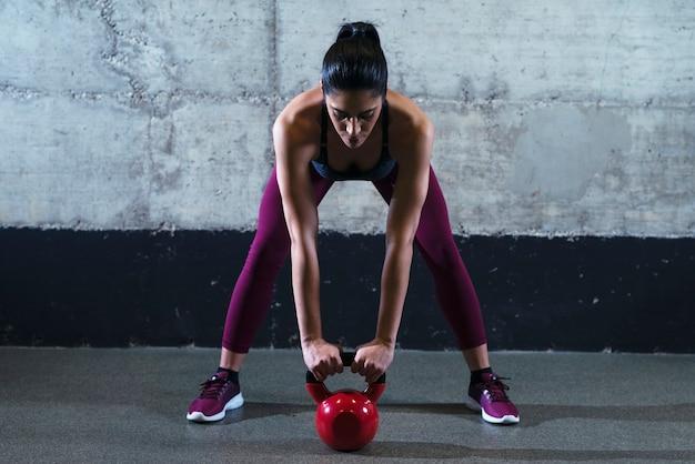 Mulher fitness em roupas esportivas se exercitando com peso de sino de chaleira na academia Foto gratuita