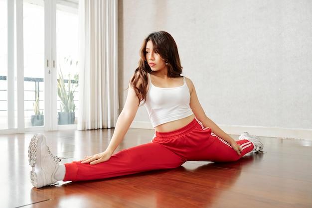 Mulher flexível desportiva praticando divisões Foto Premium