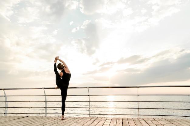 Mulher flexível fazendo yoga asana perto do mar no nascer do sol da manhã, praticando exercícios de esporte e fitness Foto Premium