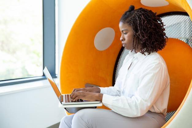 Mulher focada com dreadlocks digitando no laptop Foto gratuita