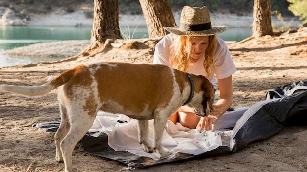 Mulher fofa e cachorro montando barraca Foto gratuita