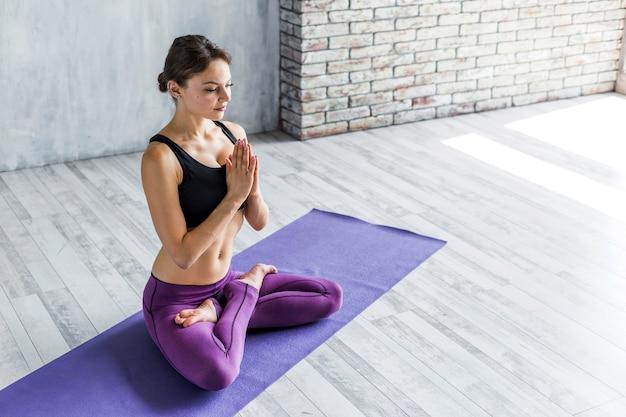 Mulher fortalecendo-a de volta em uma pose de lótus Foto gratuita
