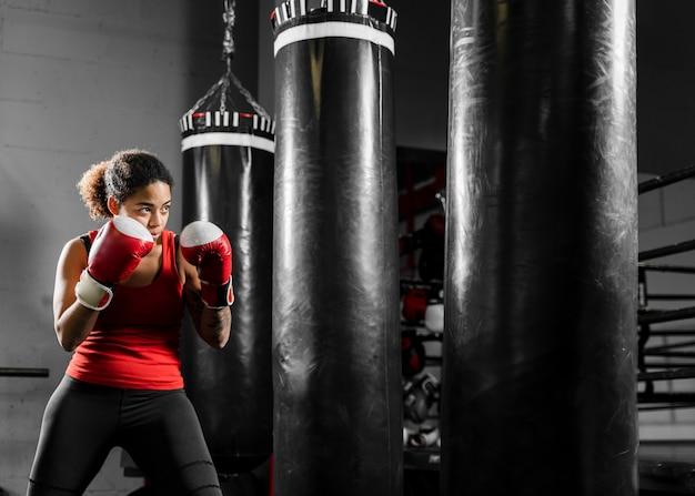 Mulher forte de treinamento no centro de boxe Foto gratuita