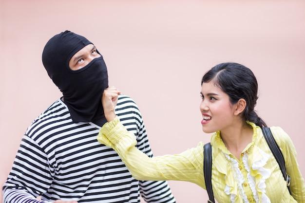 Mulher forte mulher soco e bater ladrão para proteger-se de Foto Premium