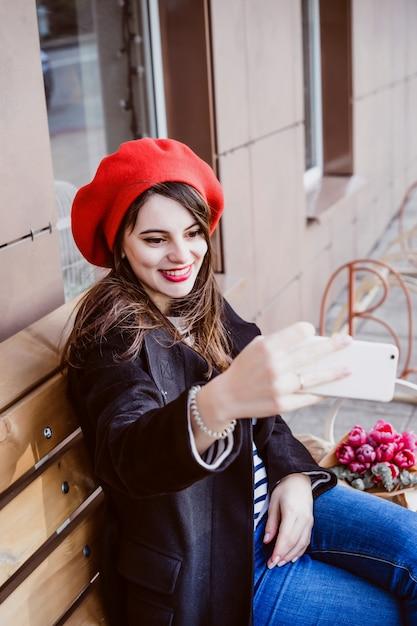 Mulher francesa em uma boina vermelha em um banco de rua  d4e405ad222