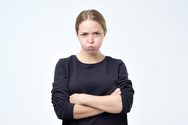 Mulher franzindo a testa em desgosto, mantendo os braços cruzados Foto Premium