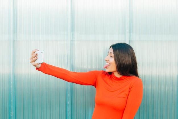 Mulher, furando, língua, levando, selfie, ligado, esperto, telefone Foto gratuita