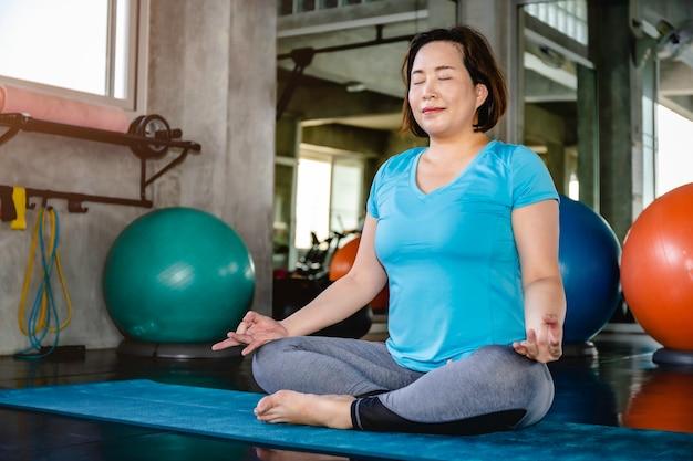 Mulher gorda sênior asiática fazendo exercícios de ioga no ginásio de fitness. Foto Premium