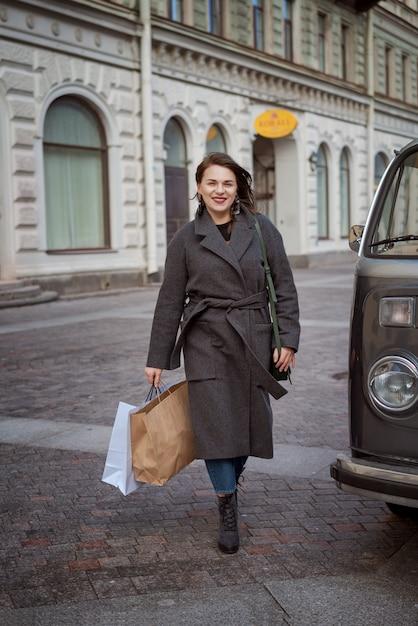 Mulher gosta de fazer compras de sucesso, andando pela rua com sacos nas mãos dela Foto Premium