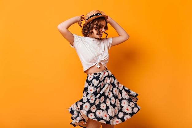 Mulher graciosa com saia da moda dançando com as mãos para cima. foto de estúdio de romântica garota encaracolada se divertindo em fundo amarelo. Foto gratuita