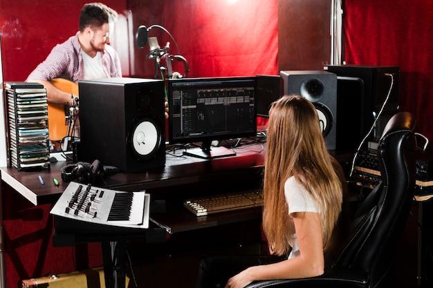 Mulher grava guitarra e cara tocando no estúdio Foto gratuita