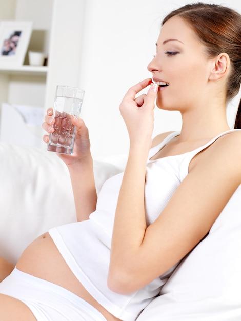 Mulher grávida aceita comprimidos e água potável Foto gratuita