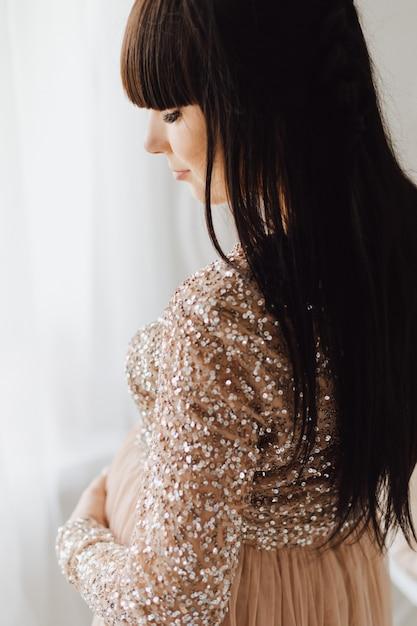 Mulher gravida bonita no vestido bege longo que está em um quarto acolhedor brilhante Foto gratuita