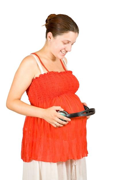 Mulher grávida com fones de ouvido na barriga Foto gratuita