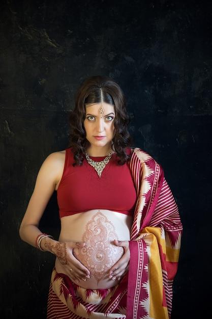 Mulher grávida com tatuagem de henna Foto gratuita