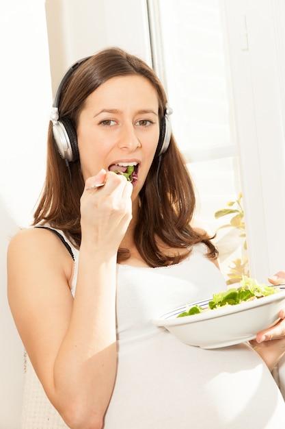 Mulher grávida comer salada e ouvir música Foto Premium