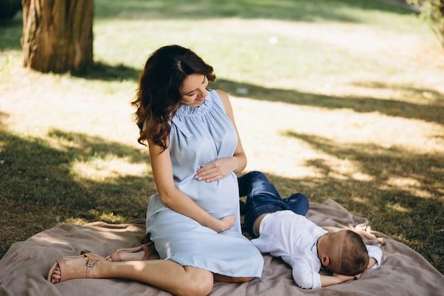 Mulher grávida, e, dela, filho pequeno, tendo piquenique, parque Foto gratuita