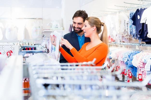 Mulher grávida, e, homem, comprando, roupas bebê, em, loja Foto Premium