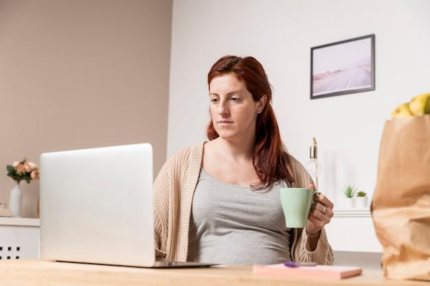 Mulher gravida em casa bebendo chá Foto gratuita