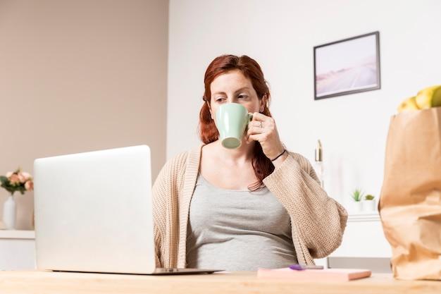 Mulher gravida em casa olhando no laptop Foto gratuita