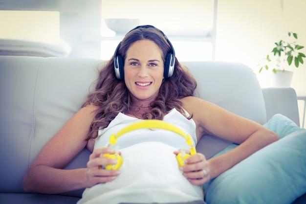 Mulher grávida, escutar música, em, sala de estar Foto Premium