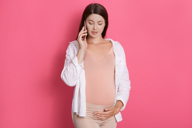 Mulher grávida falando em seu telefone inteligente e tocando, olhando para baixo, vestindo camisa branca Foto gratuita