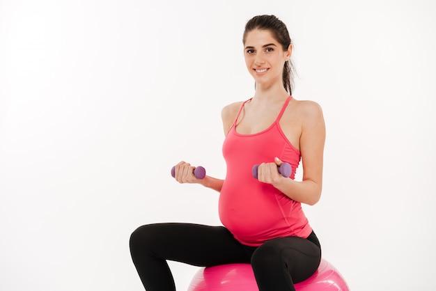 Mulher grávida fazendo exercícios com bola de ginástica e halteres Foto Premium
