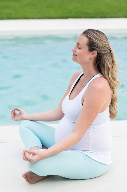 Mulher grávida, fazendo, ioga, perto, a, piscina Foto Premium