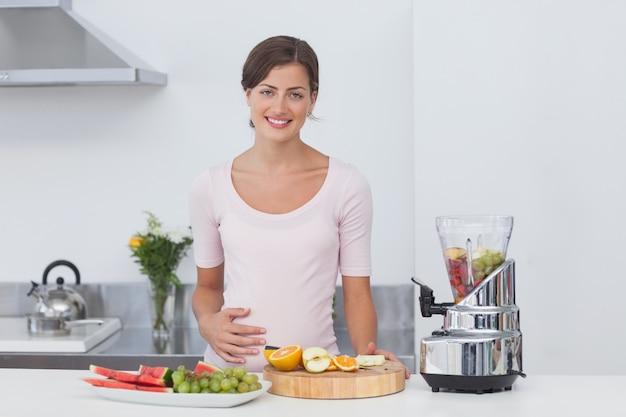 Mulher gravida fazendo um coquetel de frutas Foto Premium
