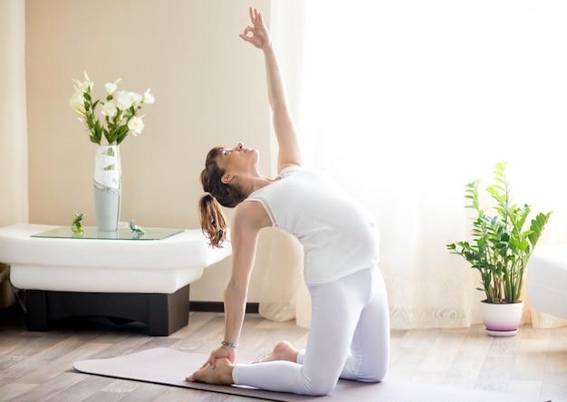 Mulher grávida fazendo ustrasana yoga pose em casa Foto gratuita