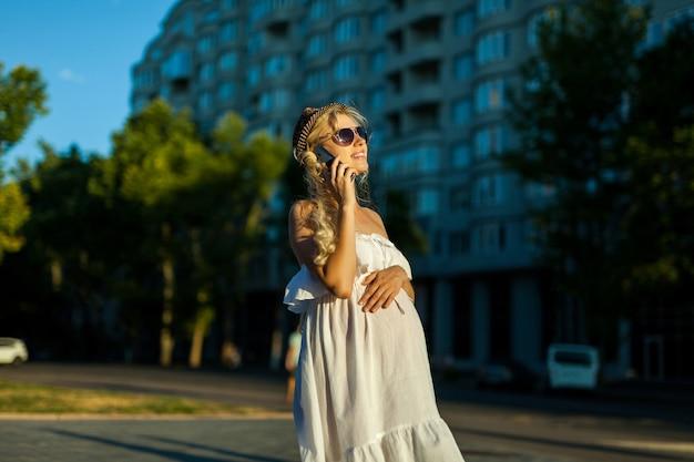 Mulher grávida feliz e caucasiana ligando para smartphone em streen na cidade Foto Premium