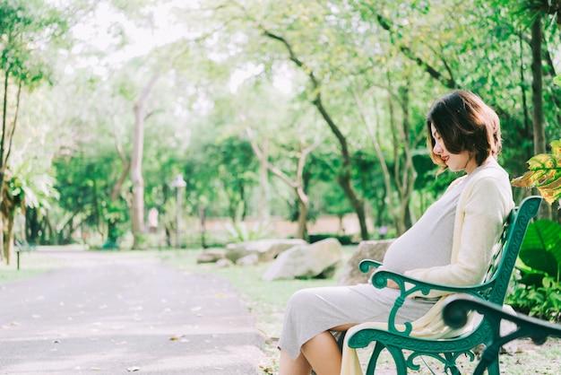 Mulher gravida feliz que relaxa fora no parque ao ar livre Foto Premium