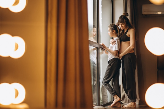 Mulher grávida, ficar, com, filha, por, a, janela Foto gratuita