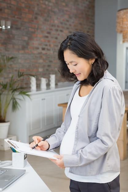 Mulher grávida, leitura, documentos, casa Foto Premium