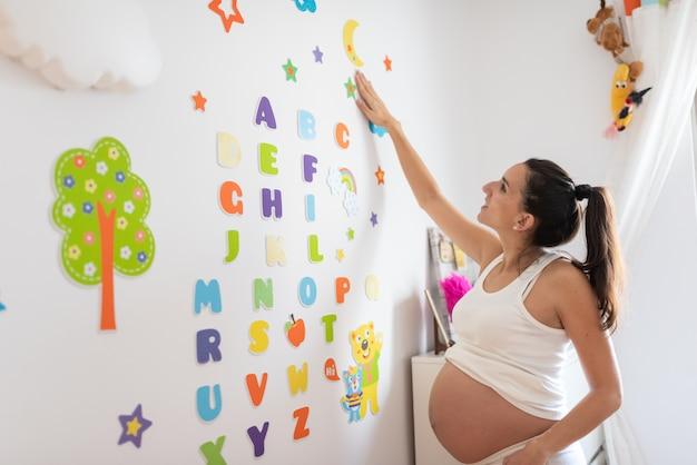Mulher grávida, lettering, a, quarto bebê, parede Foto Premium
